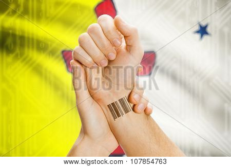 Barcode Id Number On Wrist With Canadian Province Flag On Background - Nunavut