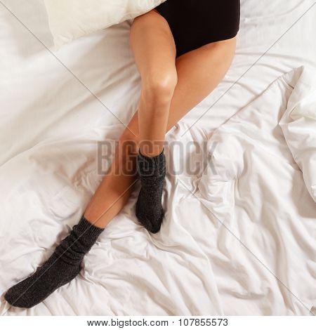 Sexy Female Legs In Socks On Bed In Bedroom