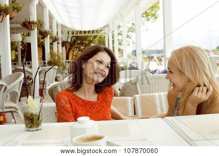 portrait of two pretty friends in cafe interior drinking and talking, chating smiling