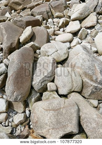 Large granite boulders and rocks on a beach shore.