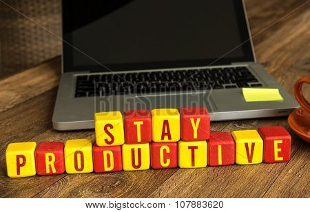 Stay Productive written on a wooden cube in office desk poster