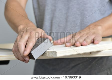 closeup of a young caucasian man sanding a wooden board with a sanding block