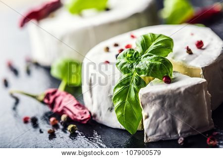 Brie cheese. Camembert cheese. Fresh Brie cheese and a slice on a granite board with basil leaves fo