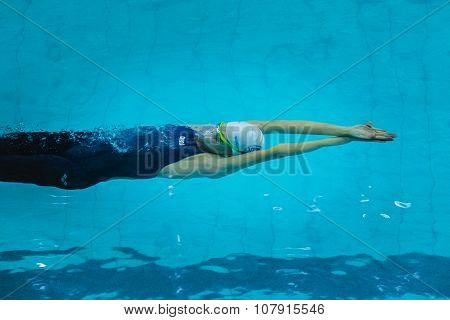 young girl swimming under water after start of  backstroke