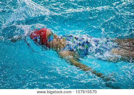 young girl swimming backstroke in pool