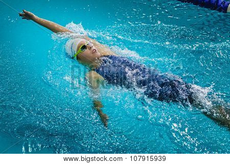 young beautiful girl athlete swims backstroke