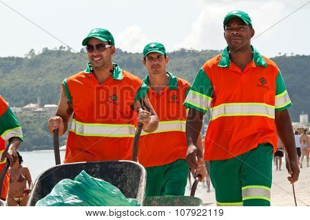 Florianopolis, SC, Brazil - Feb 5, 2012: Street-sweeper team taking care to keep the beach cleaned. The Comcap is the company hired by the city hall to execute the public cleaning service.