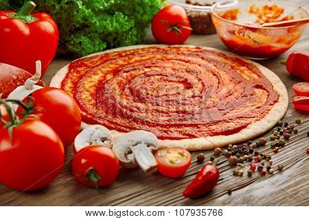 Dough basis with ketchup and ingredients for pizza, on the table poster