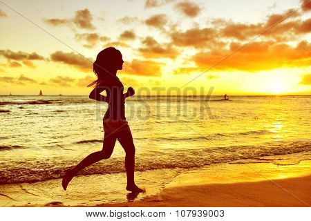 Full length of silhouette young woman jogging on shore. Side view of determined mixed race Asian / Caucasian female is running during sunrise. She is representing her healthy lifestyle.