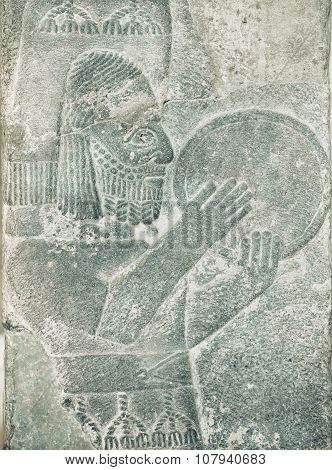 Musician with percussion instrument of Middle East. Assyrian relief on exhibition of artifacts in Pergamon Museum Berlin. poster