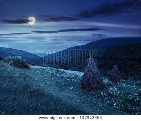 Field With Haystacks On Hillside At Night
