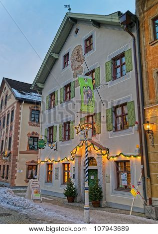 GARMISCH-PARTENKIRCHEN GERMANY - JANUARY 06 2015: Exterior of the enchanting Bavarian-styled house in Garmisch-Partenkirchen with green shutters beautiful facade painting and Christmas decoration