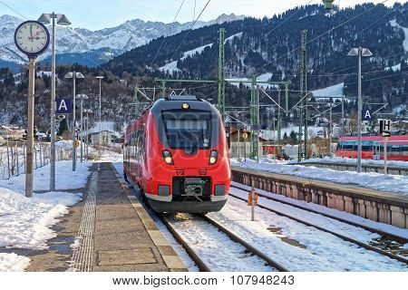 Garmisch-Partenkirchen, Germany - January 7, 2015: Train arriving at Garmisch-Partenkirchen railway station on a sunny winter day. Garmisch-Partenkirchen is a mountain resort town in Bavaria southern Germany in the heart of the Alps.