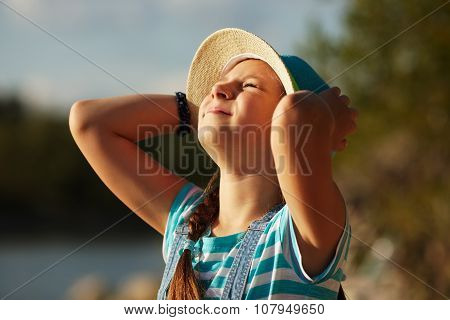 Little Girl In A Hat Squinting From The Sun