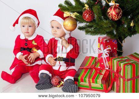 Two children under christmas pine