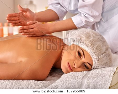 Woman 35-40 years old in spa salon receiving massage by  beautician.