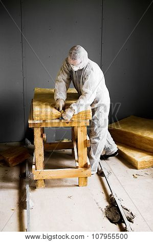 man in protective clothing and face mask cuts the glass wool for insulation of walls in an unfinished building poster
