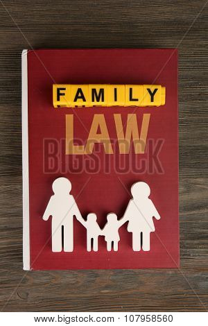 Book of law, cutout family  and blocks with letters regarding child-custody and family-law concept