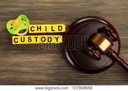 A gavel, a dummy and blocks regarding child-custody and divorce concept