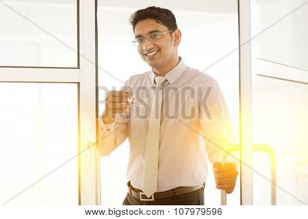 Asian Indian man holding office key, smiling and looking at camera, golden sunlight at background.