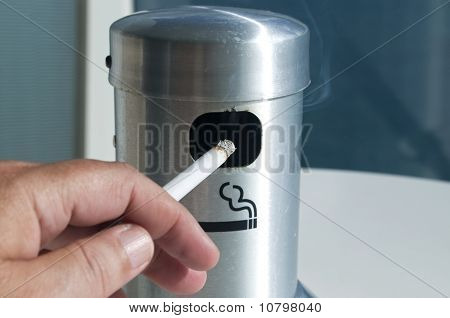 Hand holding lit Cigarette in ash tray