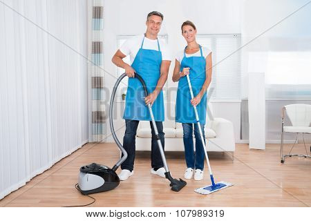 Portrait Of Two Happy Janitors With Vacuum Cleaner And Mop poster