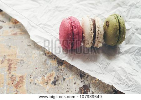 Three Macaroon Cakes On Crumpled Paper And Rustic Table