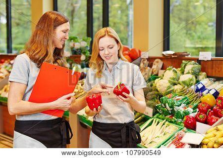 Salesclerk in training getting help from staff in a supermarket
