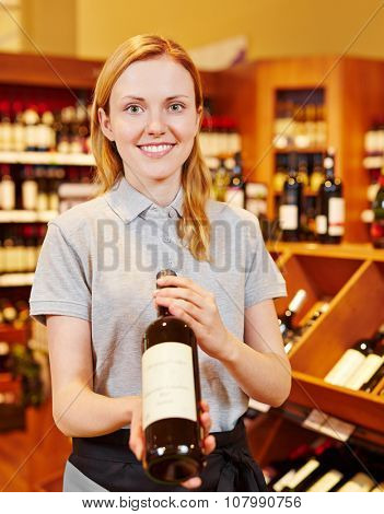 Smiling sommelier in wine shop recommending bottle of red wine