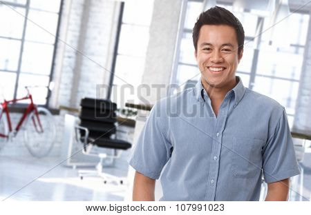 Portrait of happy asian office worker at trendy workplace.
