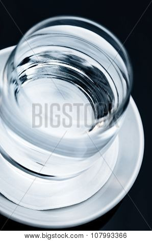 Single glass of clean clear drinking water tilted tilt view close up macro on the table