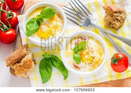 Egg cocotte  in white ramekin with tomato and basil