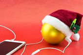 Christmas ball with Santa's hat and smartphone with earphones on red with copy-space poster