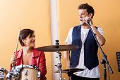 Happy male singer performing while looking at female drummer in recording studio poster