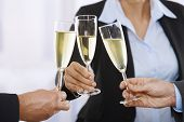 Close-up of hands: husiness people raising toast with champagne focus placed on flutes. poster