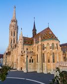 The outside of Matthias Church in Budapest Hungary during the day shownig the gothic architecture. poster