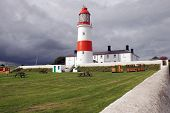 Storm clouds gathering over Souter Lighthouse in the North East of England poster