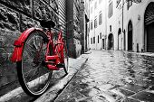 Retro vintage red bike on cobblestone street in the old town. Color in black and white. Old charming bicycle concept. poster