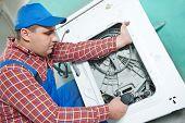 Washing machine repair. Repairer replacing electric engine motor in damaged unit  poster