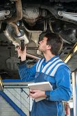 A mechanic, checing a muffler on an exhaust system of a modern car on a car lift using a LED flashlight, for gas leaks during a periodic inspection or MOT test poster