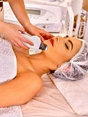 Young woman receiving electric ultrasonic peeling facial treatment  at beauty salon. Close up. poster
