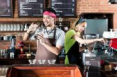 Woman and man in Asian cafe preparing coffee and smelling on fresh coffee beans poster