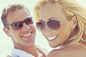 Instagram style photograph of happy and attractive man and woman couple wearing sunglasses and smiling in sunshine at the beach poster