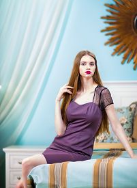 Beautiful Woman In Purple Dress In Luxury Bedroom Interior.