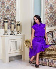 Beautiful Woman In Purple Dress In Luxury Interior.