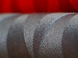 Closeup of reel of silver thread with red in the background