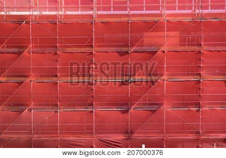 scaffolding on a building construction site covered with red safety netting photographed in New Zealand NZ
