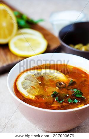 Solyanka is a Russian meat soup with olives and lemon from several types of meat in a deep plate.