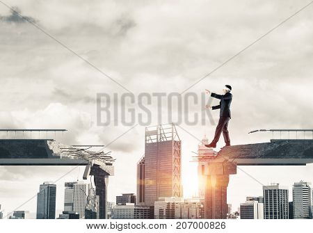 Businessman walking blindfolded on concrete bridge with huge gap as symbol of hidden threats and risks. Cityscape view with sunlight on background. 3D rendering.