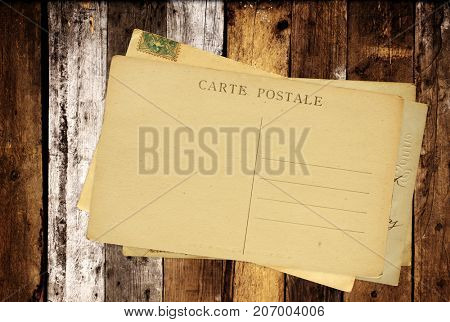Vintage post cards on old wooden planks. Inscription on the card - carte postale - postcard in french